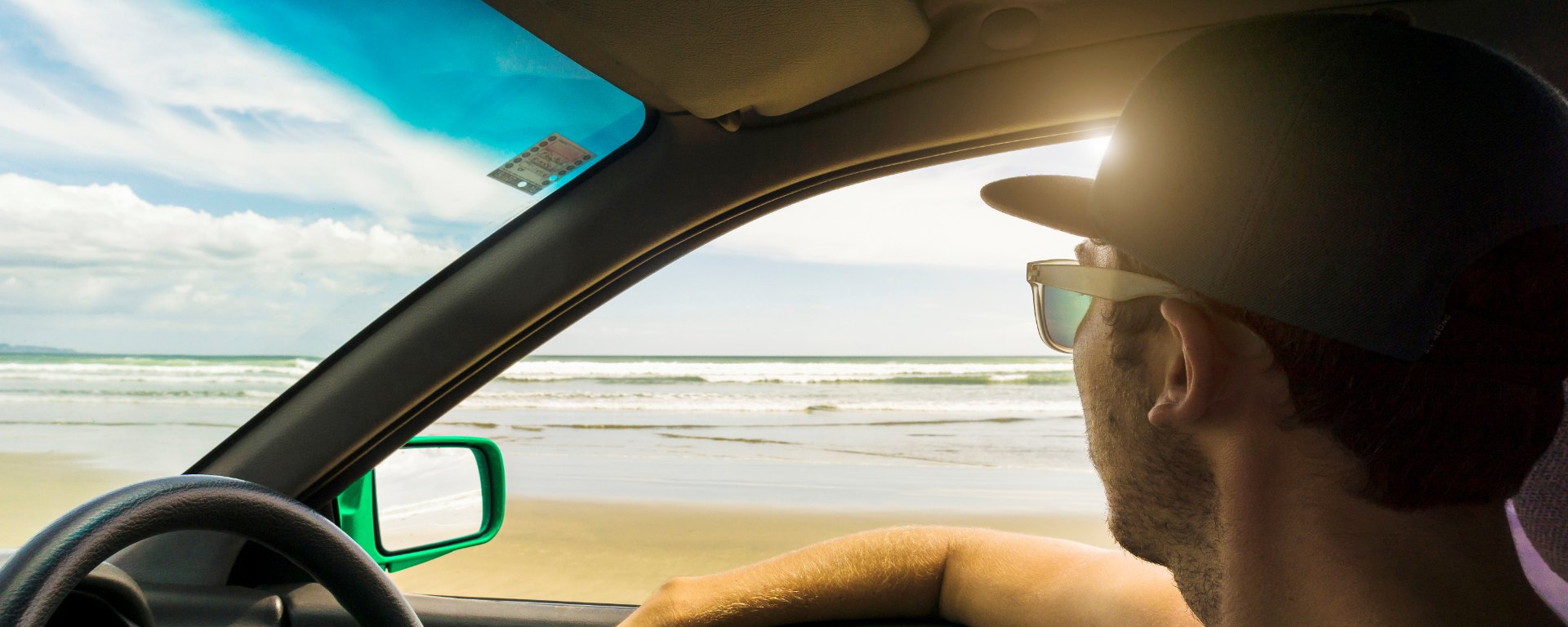 A man sits in his green car looking at the beach on a sunny day