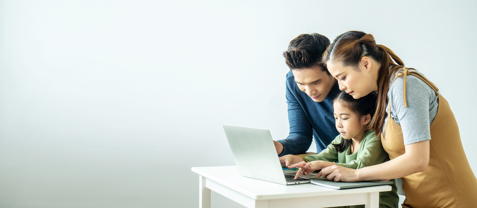 man, woman, and young girl looking at laptop